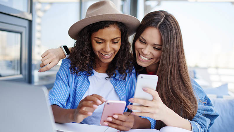 two female friends smiling looking at mobile phones