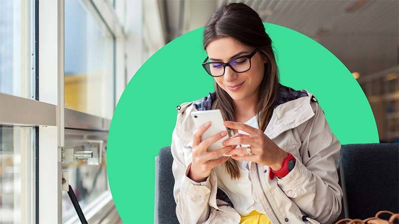 woman looking at mobile phone smiling