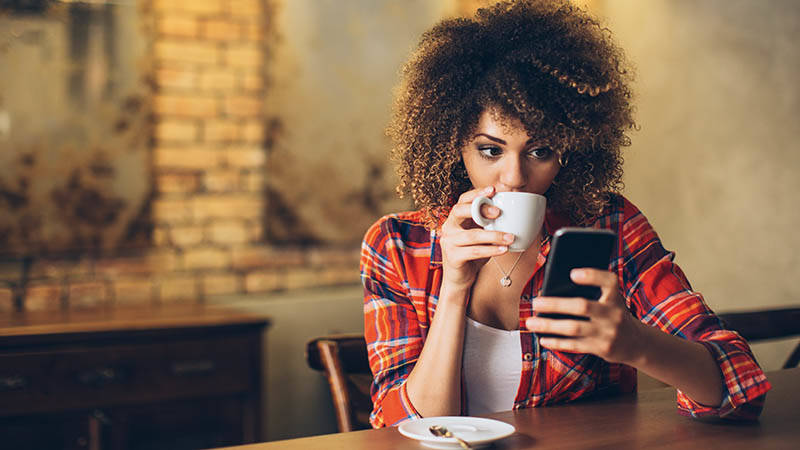 young woman drinking coffee while looking at mobile phone